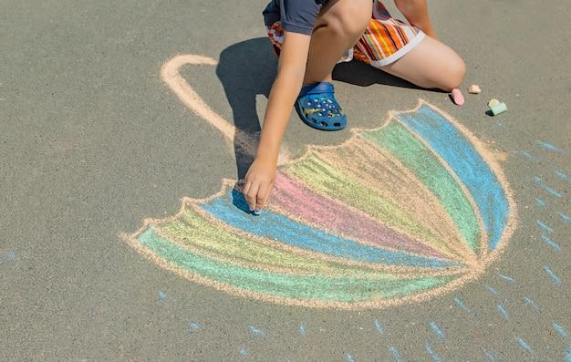 Niño dibuja con tiza en el pavimento