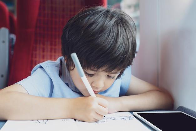 Niño dibujando o viendo dibujos animados en tableta sentado junto a la ventana.