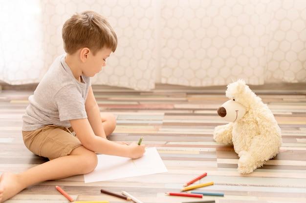Niño dibujando en el piso