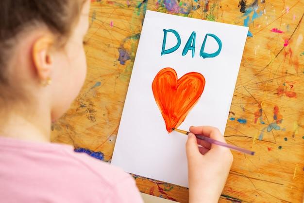 Niño está dibujando la tarjeta de felicitación del día del padre.
