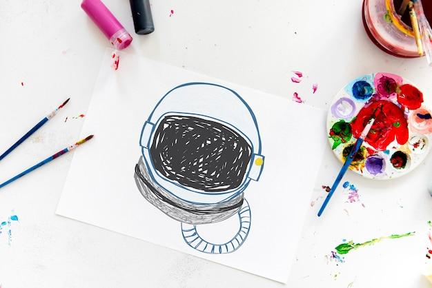 Niño con un dibujo de casco de astronauta.