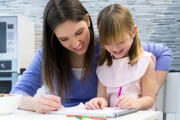 Niño dibujo con lápices de colores con su mamá en casa