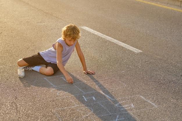 Niño, dibujo, rayuela, en, asfalto, camino