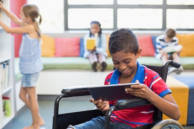 Niño discapacitado en silla de ruedas con tableta digital en la biblioteca