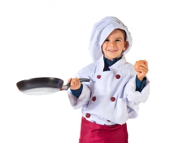 Niño disfrazado de chef sosteniendo una sartén frita.
