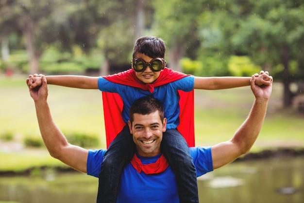 Niño disfrazado de superhéroe sentado en el hombro del padre