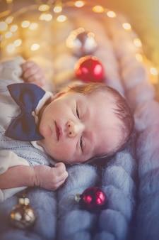 Niño disfrazado tumbado con decoración navideña.