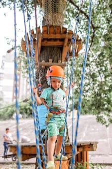 Niño disfrutando del tiempo en una estructura de cuerda en el parque de aventura