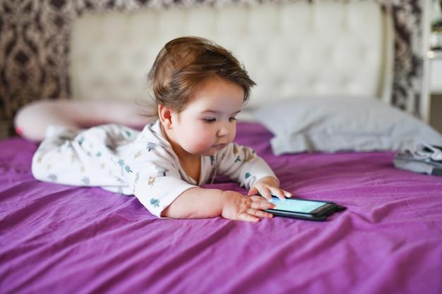 Niño y dispositivo móvil. niña en la cama mirando un teléfono inteligente