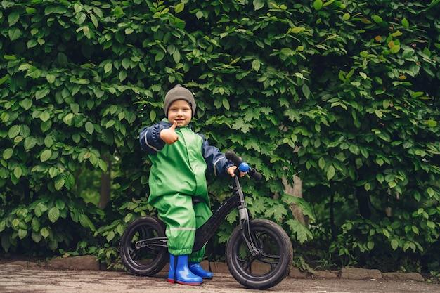 Niño divertido en botas de lluvia jugando en un parque de lluvia
