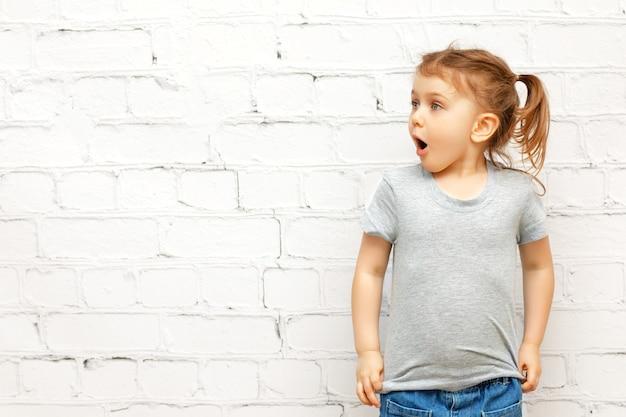 Niño divertido emocionado con cara de expresión en ropa casual sobre la pared y mirando el espacio de la copia.