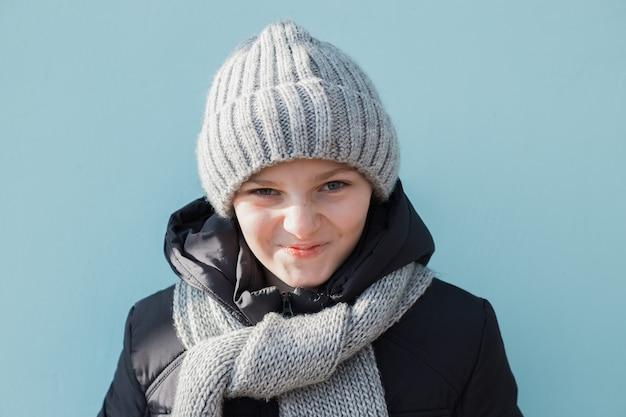 Niño divertido enojado y disgustado listo para las vacaciones de invierno. chico de moda en invierno gorro gris y bufanda de pie contra la pared azul.