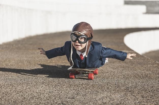 Niño divertido jugando con alas de juguete al aire libre.