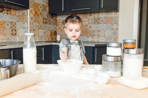 Niño divertido de pie en una cocina rústica jugando con harina. está cubierto de harina y se ve gracioso.