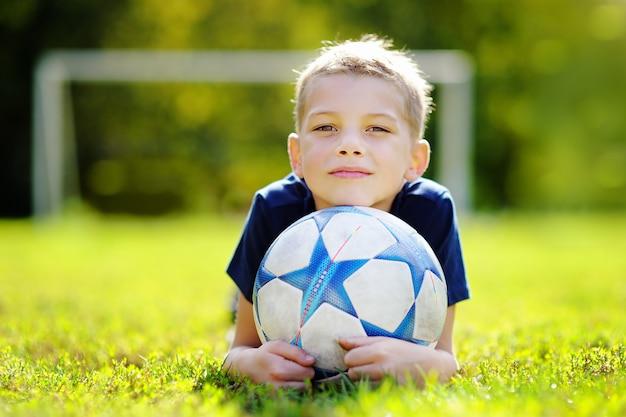 Niño divirtiéndose jugando un partido de fútbol en un día soleado de verano