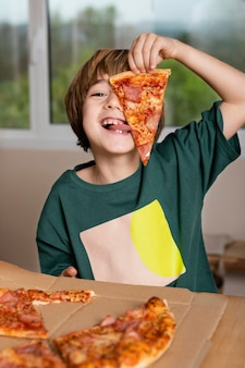 Niño divirtiéndose mientras come pizza