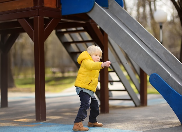 Niño divirtiéndose en el patio al aire libre en la primavera o el día de otoño