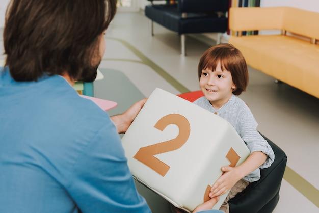 Niño y doctor jugando juego educativo en clínica