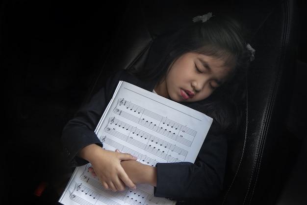 Niño dormido con nota musical en el asiento del automóvil como música de amor