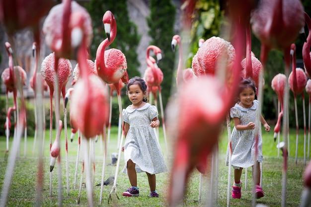 Niño dos niñas corriendo y divirtiéndose en el parque de la estatua de flamenco