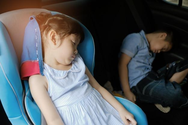 El niño duerme en el auto, el niño se siente enfermo, duerme en el asiento del auto