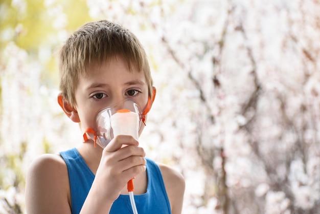 Niño en edad escolar hace la inhalación en casa. prevención