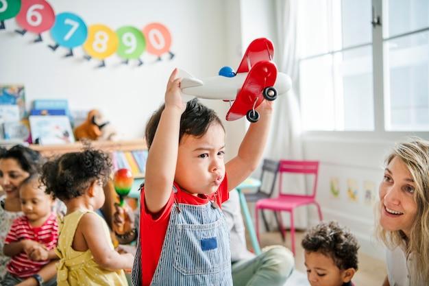 Niño en edad preescolar disfrutando jugando con su avión de juguete