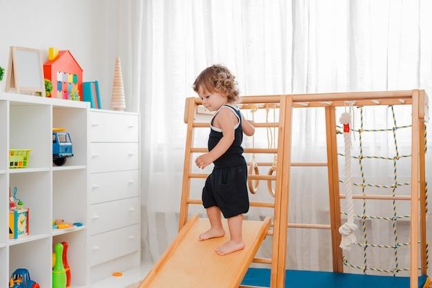 El niño a una edad temprana de 1.5 años participa en el complejo deportivo de madera para niños en el hogar.