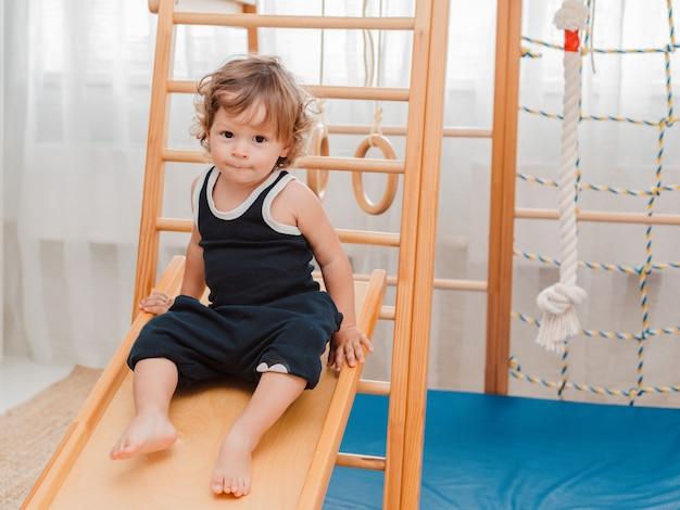 El niño a una edad temprana participa en el complejo deportivo de madera para niños en el hogar.
