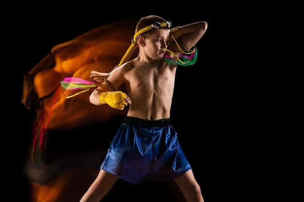 Niño ejercicio de boxeo tailandés en pared negra. luz mixta. luchador practicando artes marciales en acción, movimiento. evolución del movimiento, momento de captura. juventud, deporte, concepto de cultura asiática.