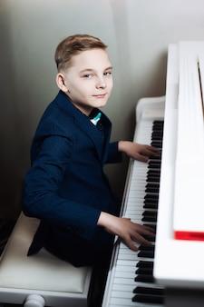 Niño elegante aprende a tocar un instrumento musical