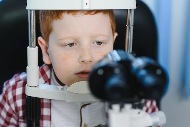 Niño eligiendo gafas en la tienda de óptica.