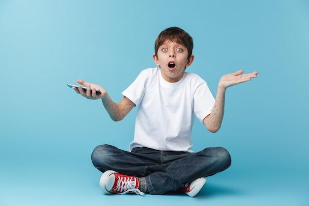 De niño emocionado europeo con pecas vistiendo camiseta blanca casual sosteniendo y usando el teléfono inteligente mientras está sentado en el piso aislado sobre la pared azul