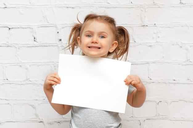 Niño emocionado sobre pared de ladrillo blanco sosteniendo la hoja de papel vacía en blanco