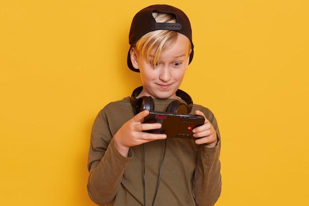 Niño emocional y activo con cabello rubio, llevando su dedo en la pantalla del teléfono inteligente mientras juega su juego favorito en línea