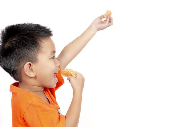 Niño en traje naranja comer naranja aislado sobre fondo blanco