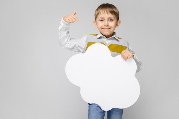 Un niño encantador con una camisa blanca, camiseta sin mangas a rayas y jeans claros se alza sobre un fondo gris. el niño sostiene un cartel blanco en forma de nube.