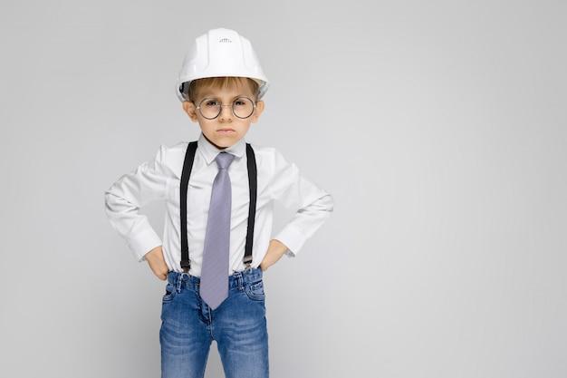 Un niño encantador con una camisa blanca, tirantes, corbata y jeans claros se alza sobre un fondo gris. niño con un casco blanco