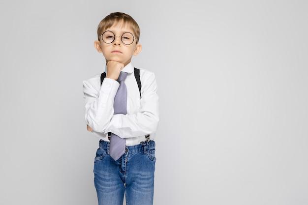 Un niño encantador con una camisa blanca, tirantes, corbata y jeans claros se alza sobre un fondo gris. el niño puso la barbilla sobre el puño.