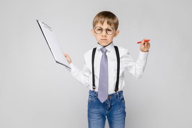 Un niño encantador con una camisa blanca, tirantes, corbata y jeans claros se alza sobre un fondo gris. el niño sostiene un bolígrafo y hojas para notas.