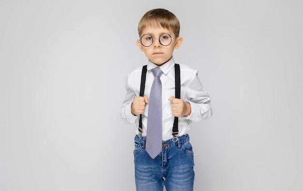 Un niño encantador con una camisa blanca, tirantes, corbata y jeans claros se alza sobre un fondo gris. el niño sostiene sus manos por frenos