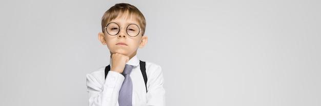 Un niño encantador con una camisa blanca, tirantes, corbata y jeans claros se alza sobre un fondo gris