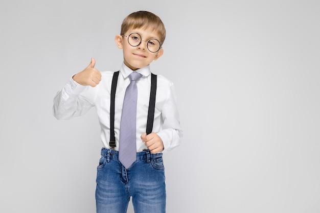 Un niño encantador con una camisa blanca, tirantes, corbata y jeans claros se encuentra en una pared gris.