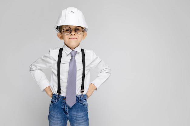 Un niño encantador con una camisa blanca, tirantes, corbata y jeans claros se levanta sobre un gris. niño con un casco blanco