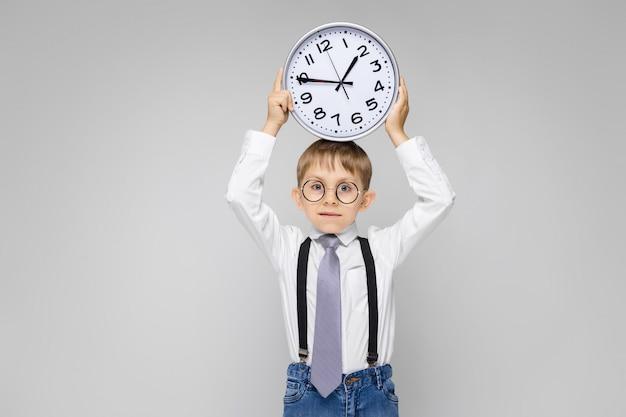 Un niño encantador con una camisa blanca, tirantes, corbata y jeans claros se levanta sobre un gris. un niño sostiene un reloj en su cabeza.