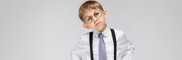 Un niño encantador con una camisa blanca, tirantes, corbata y jeans ligeros se destaca en gris. el chico de anteojos inclinó la cabeza hacia un lado