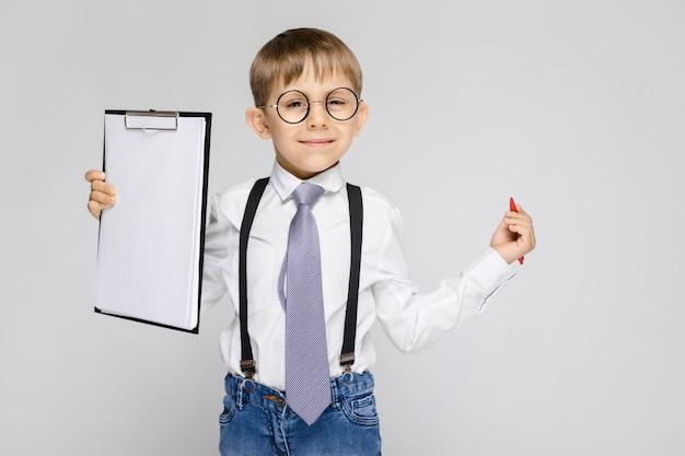 Un niño encantador con una camisa blanca, tirantes, corbata y jeans ligeros se destaca en gris. el niño sostiene un bolígrafo y hojas para notas.