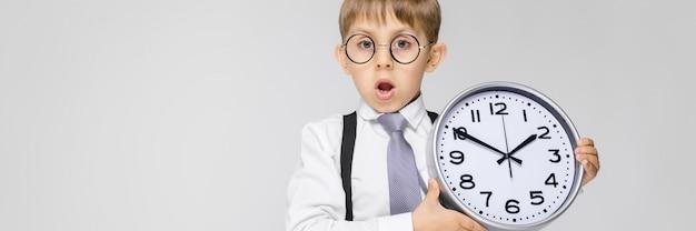 Un niño encantador con una camisa blanca, tirantes, corbata y jeans ligeros se destaca en gris. el niño sostiene un reloj