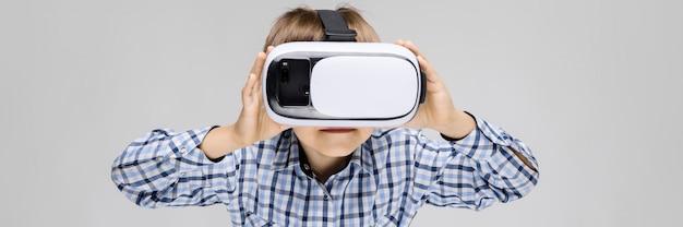 Un niño encantador con una camisa con incrustaciones y jeans claros se alza sobre un fondo gris. el niño en su cara gafas realidad virtual