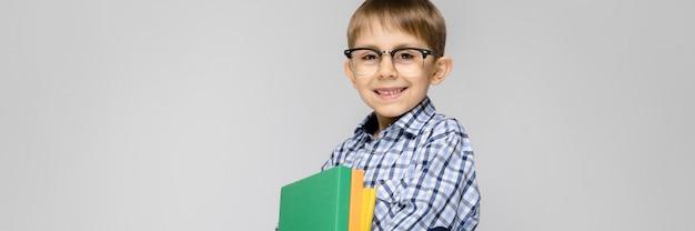 Un niño encantador con una camisa vkletchatoy y jeans claros se alza sobre un fondo gris